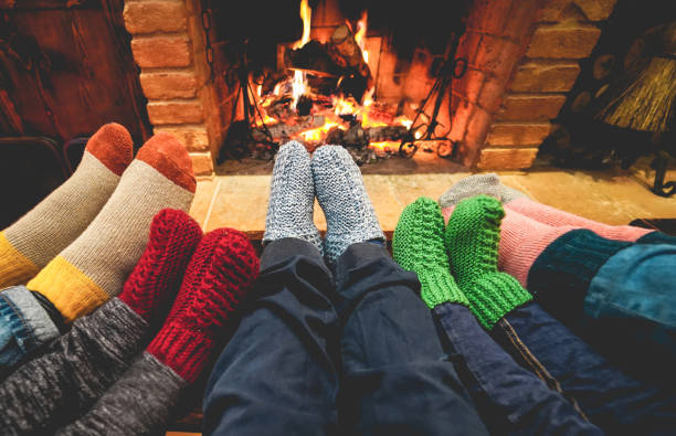 Legs view of happy family wearing warm socks in front of fireplace